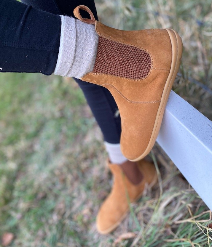 A close up of a woman's feet wearing Vivobarefoot Fulham barefoot chelsea boots in desert sand nubuck with one foot on the ground and one foot on a white fence.