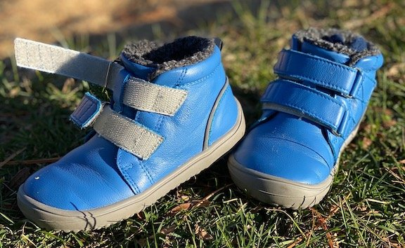 a pair of kids barefoot winter shoes from Be Lenka, the Penguin model in bright blue, lined with fleece sitting on grass.
