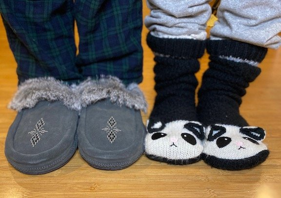 two pairs of feet standing side by side. One is wearing barefoot manitobah mukluk moccasin slippers, and the other is wearing slipper socks