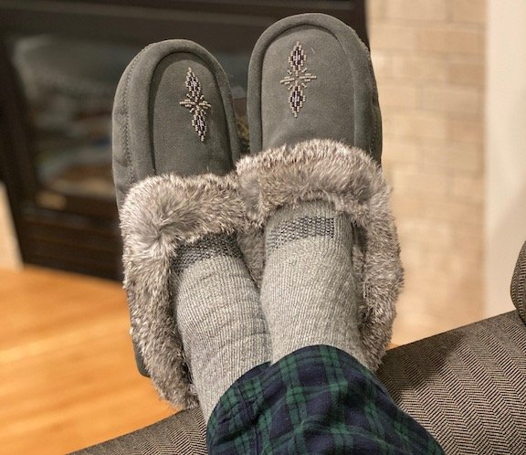 a pair of feet propped up wearing barefoot manitobah mukluk moccasin slippers