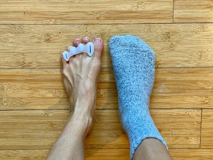 a top down view of a pair of feet wearing Correct Toes. One foot is bear and the other is wearing a barefoot socks
