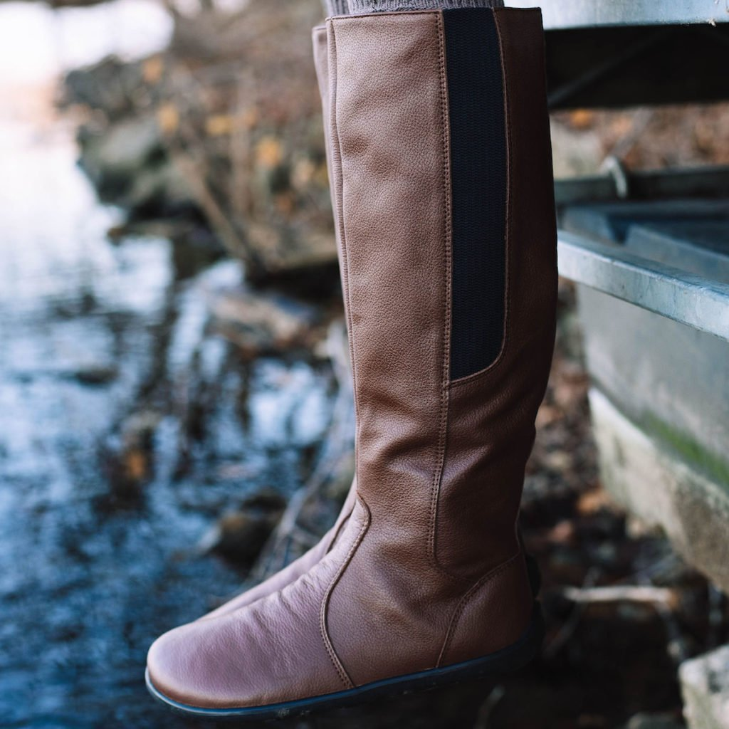 A pair of legs hanging off a dock while wearing Be Lenka Sierra brown leather riding barefoot boots