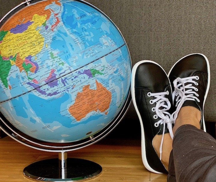 A close up of a globe of the world with a pair of feet wear Be Lenka barefoot Prime sneakers from Anya's Shop