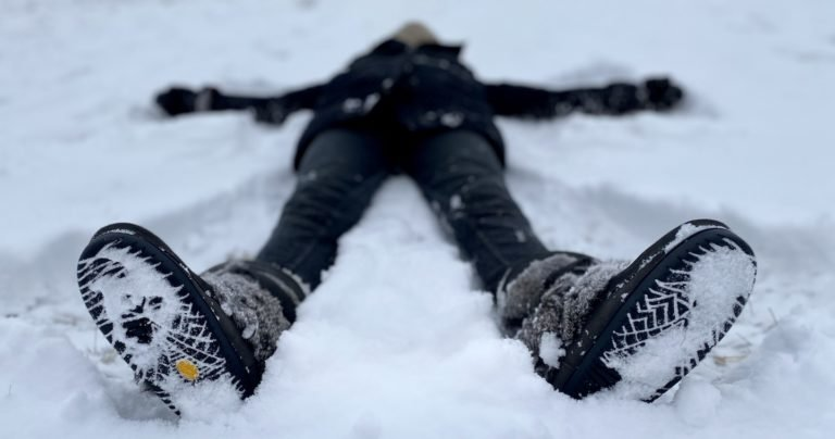 A blurry figure laying on their back in the show, wearing Manitobah Mukluks winter boots, showing the snowy vibram outsole bottoms