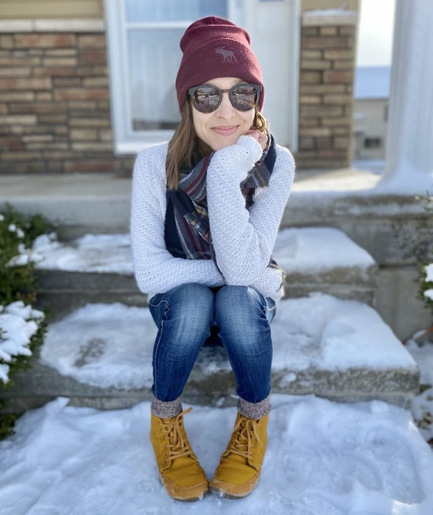 A woman sitting outside on a snowy porch smiling at the camera wearing warm clothes and Wildling shoes winter model honeybear