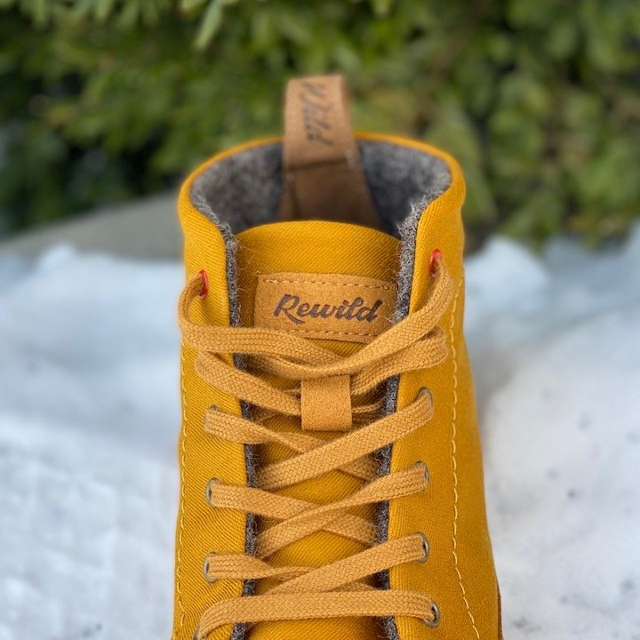 Close up of one lace up winter barefoot boot outside with a snowy background, Wildling Honeybear