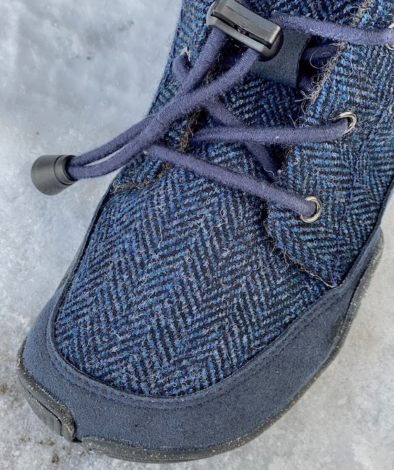 A close of up the toe box of the Nessie kids winter barefoot shoe from Wildling showing the blue houndstooth pattern and elastic laces.