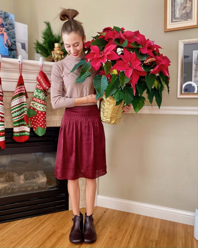 A woman dressed up in a deep red skirt, and burgundy dress ankle boots, Shapen Ivy, smiling and holding a Christmas Poinsettia