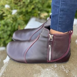 Close up side view of a woman's feet wearing Shapen Ivy Bordeaux dressy ankle boots with jeans