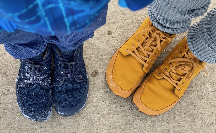 A top down view of two pairs of feet standing in snow covered wildling shows. One is a child wearing the Nessie, and the other is an adult wearing the Honeybear.