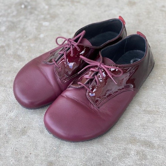 A close up photo of the Shapen Barefoot Fleur, a barefoot oxford in maroon color.