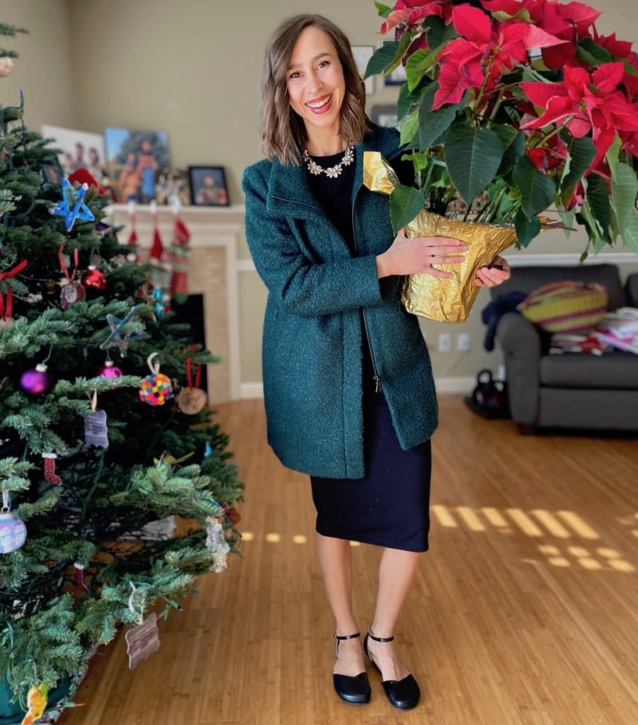 A woman standing next to a Christmas tree wearing Shapen Barefoot black poppy flats sandals, the best dressy barefoot flats for women.
