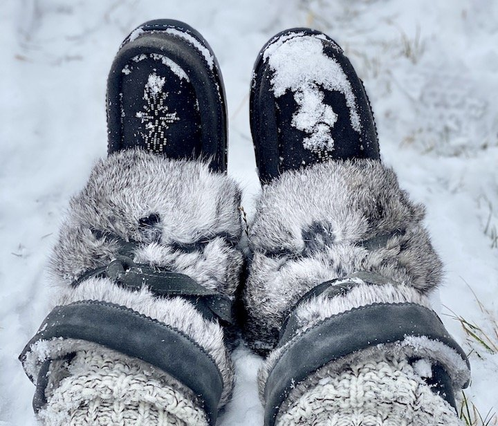 A pair of feet in deep snow wearing the warmest barefoot winter boots, Manibotah Mukluks