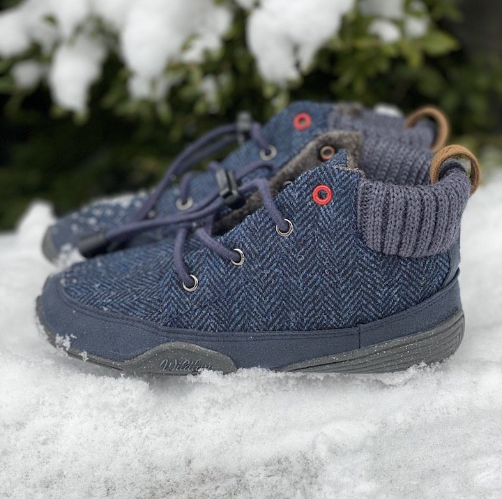Close up side view of Wildling Nessie kids barefoot boots sitting on top of snow