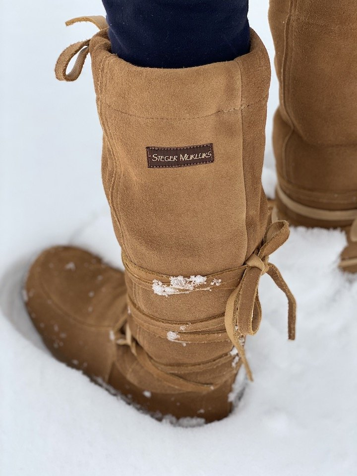 A side view of a pair of feet wearing steger mukluks review in deep winter snow