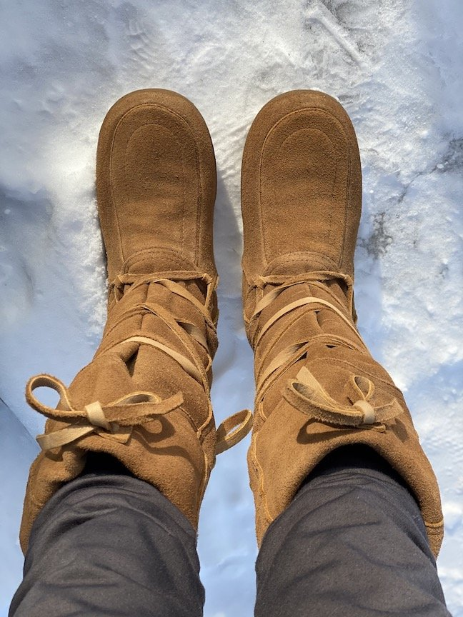 A pair of feet wearing Steger Mukluks with barefoot feeling standing on winter snow