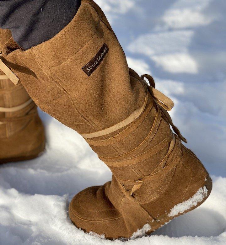 A pair of Steger Mukluks walking through snow