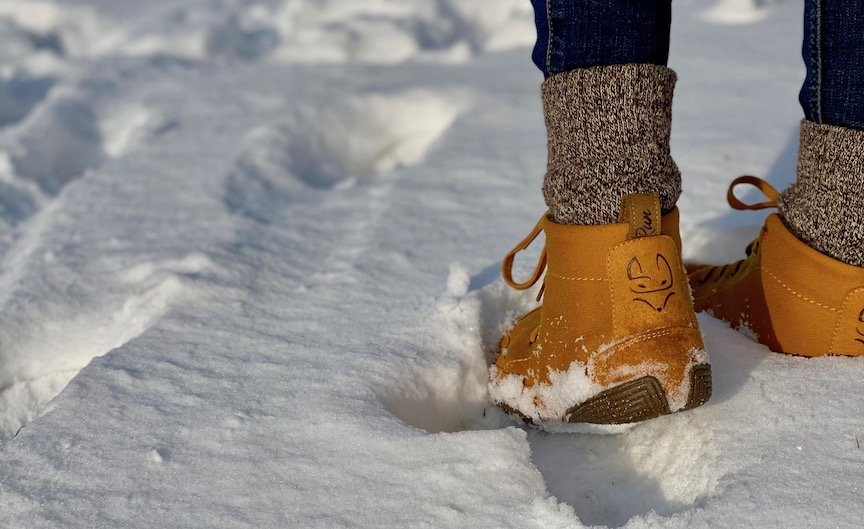 A close up image of a pair of feet from behind standing in snow that is a few inches deep. She is wearing a pair of Wildling shoes honeybear wool lined warm barefoot winter shoes.