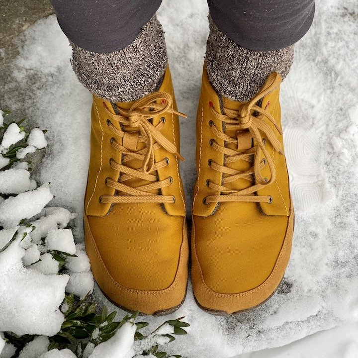 A pair of legs wearing Wildling Honeybear wool lined flexible lace up winter barefoot boots