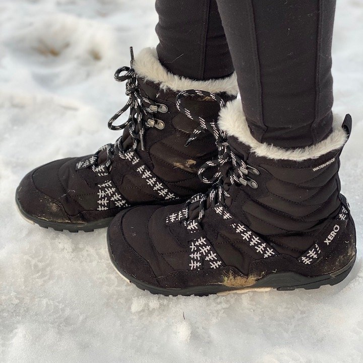 A side view of a woman's foot wearing Xero's Alpine vegan barefoot snow boot, waterproof and warm.