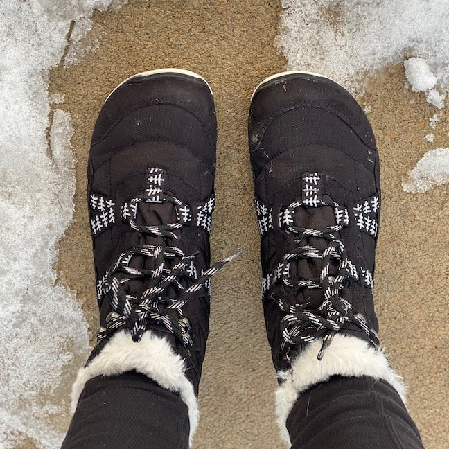 A top down view of a pair of feet wearing the vegan Xero shoes Alpine barefoot winter snow boots in black