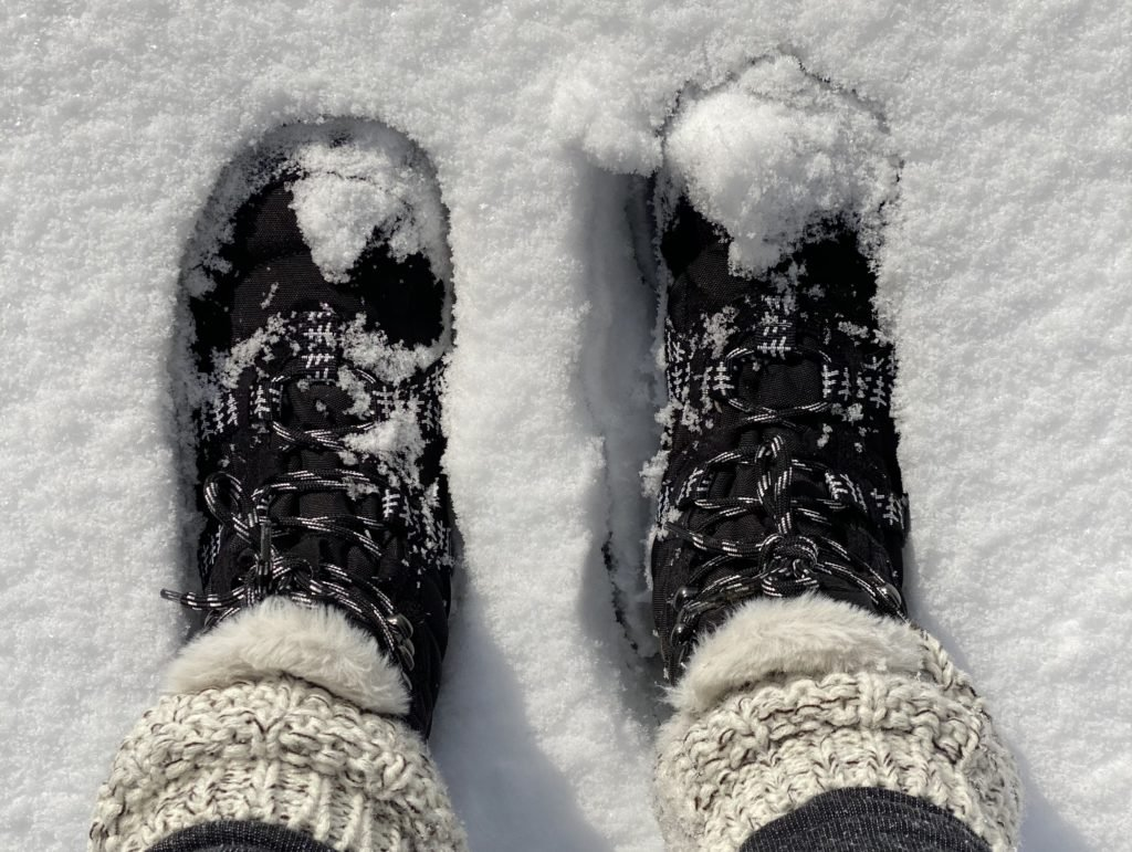 A top down view of a pair of feet wearing the xero shoes vegan barefoot winter snow boot the Alpine standing in deep snow