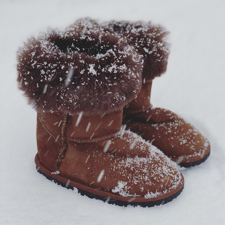 A pair of little kid Zeazoo boots sitting outside during snowfall. The sheepskin cuff is folded over and snow is gathering on the toes.