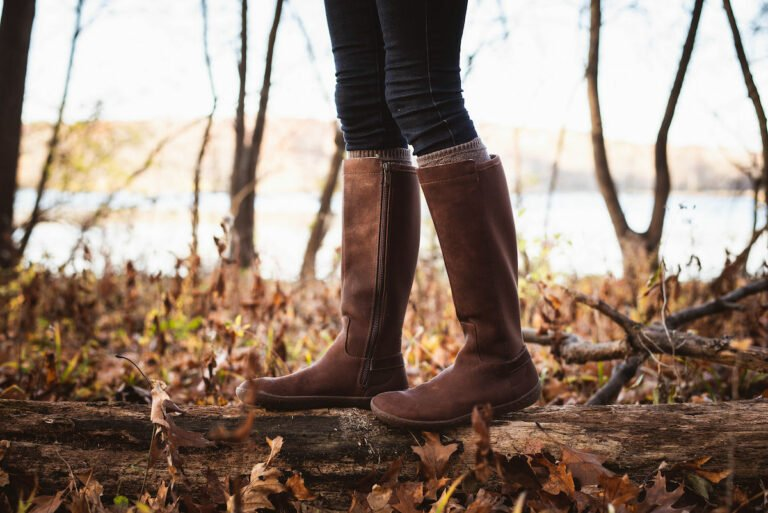 A close up of a woman walking on a log in the woods while wearing Vivobarefoot Ryder boots, a popular tall leather barefoot boot.