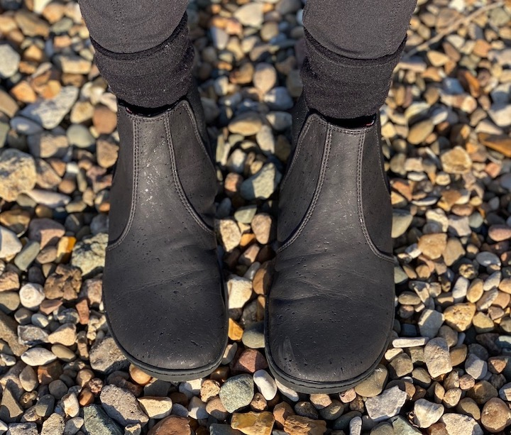 A pair of feet wearing vegan Mukishoes Chelsea barefoot boots in a review.