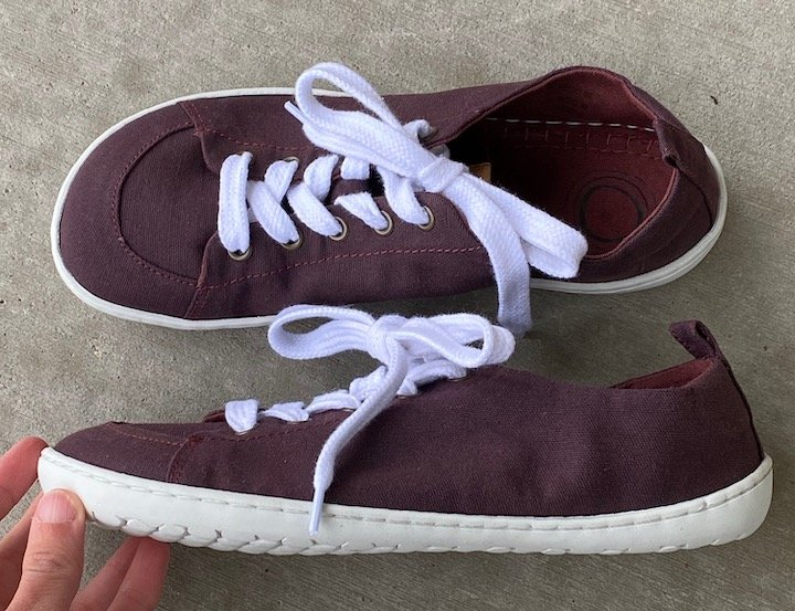 A pair of plum barefoot sneakers from Mukishoes. One sneaker is turned sideways to show the completely flat sole and the other shows the foot shaped top.