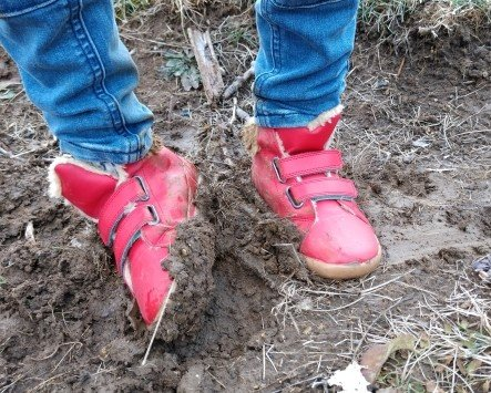 A little boy's leg wearing Ten Little Everyday High Top shoes standing in mud.