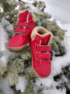 A pair of Lava Red High tops from Ten Little sitting on an ice covered pine tree.