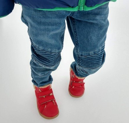 A little boy's legs standing on snow in jeans and red Ten Little High Top sneakers.