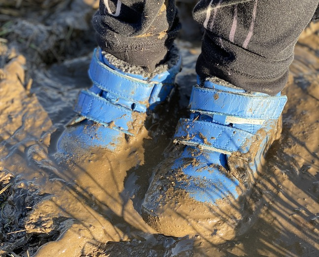 A kid wearing Be Lenka Penguin Boots standing in very mucky mud