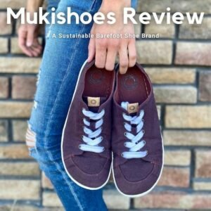 """A woman holding a pair of Mukishoes Plum sneakers at her side in front of a brick wall. The text reads, """"Mukishoes Review, a sustainable barefoot shoe brand."""""""