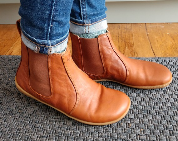 A woman in cuffed skinny jeans wearing Mukishoes Chelsea Caramel leather barefoot boots