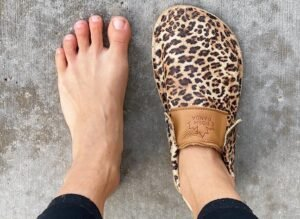 Close up of a woman's feet with one Posh Panda Moccasin on her right foot, her left foot is bare to show how they are foot shaped.