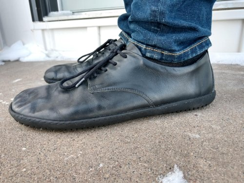 A close up side view of a man's feet wearing Groundies Palermo black leather dress shoes.
