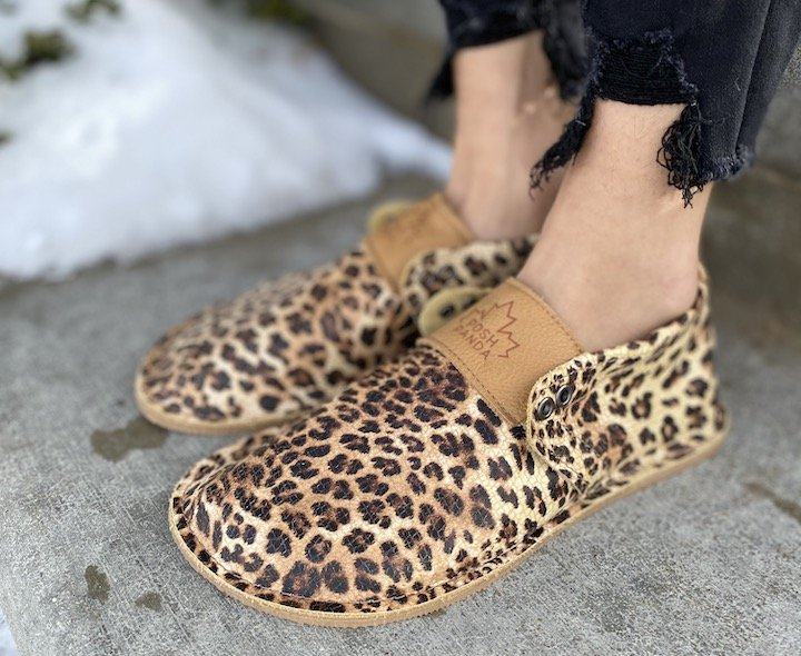 A close up angled view of a pair of Posh Panda leopard barefoot moccasins.