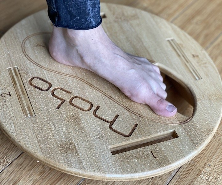 A close up of a woman's foot on a Mobo Balance Board