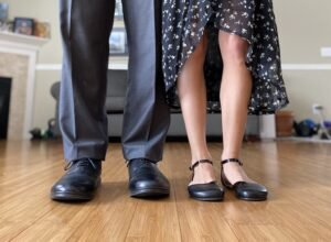 A photo of a husband and wife's legs wearing very dress barefoot shoes. The man is in Carets Dress shoes and the woman is in Shapen Poppy flats
