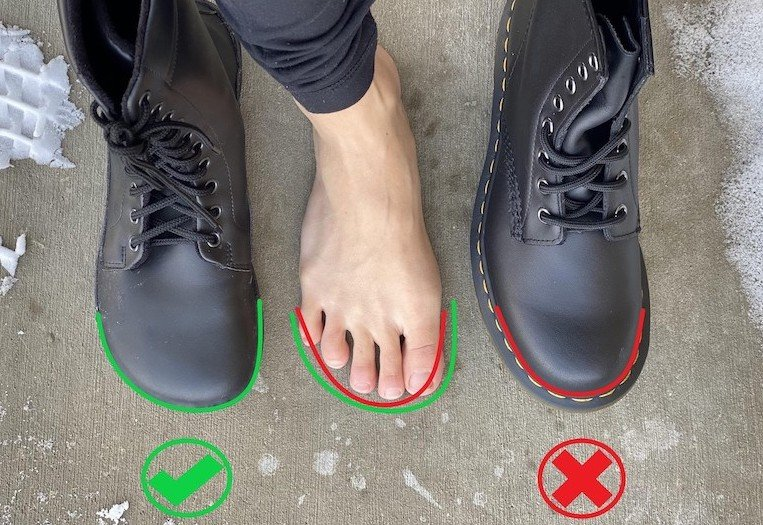 barefoot combat boots - A top down view of a woman's foot standing between one Ahinsa barefoot boot and one Doc Marten Boots. There are green and red lines showing the toe box shapes of both. Ahinsa is foot shaped, and Doc marten tapers to squish the toe.