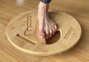 A close up front view of a woman's foot on the Mobo balance board, designed to strengthen balance skills.