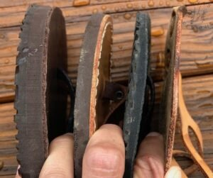 Closeup of a hand holding 4 pairs of sandals separated by their fingers to show varrying thickness among barefoot sandal brands