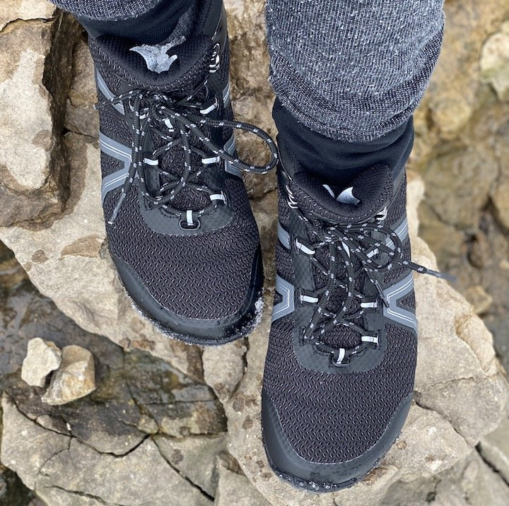 A top down view of a person wearing Xero Xcursion barefoot hiking boots climbing on rocks.