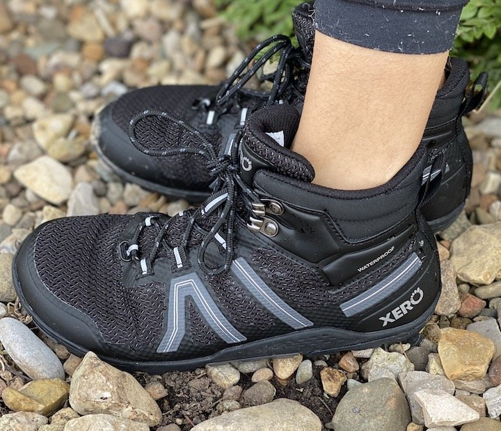 A side angled view of a pair of legs wearing Xero Xcursion waterproof hiking boot