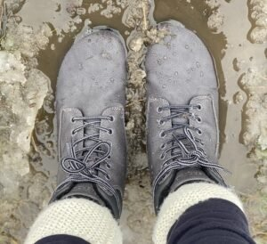 A top down close up of Feelgrounds Patrol, a vegan barefoot winter boots, standing in a puddle of yucky muddy snow.
