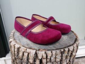 A close up of a pair of velvet vegan burgundy Ballet Pumps by tadeevo sitting unworn on a tree stump.