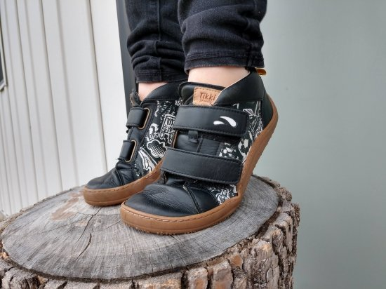 A close up of a kids feet wearing Tikki Moon black leather sneakers in Graffiti print standing on a log on their tiptoes showing the easy flexibility of these super cool barefoot shoes for kids