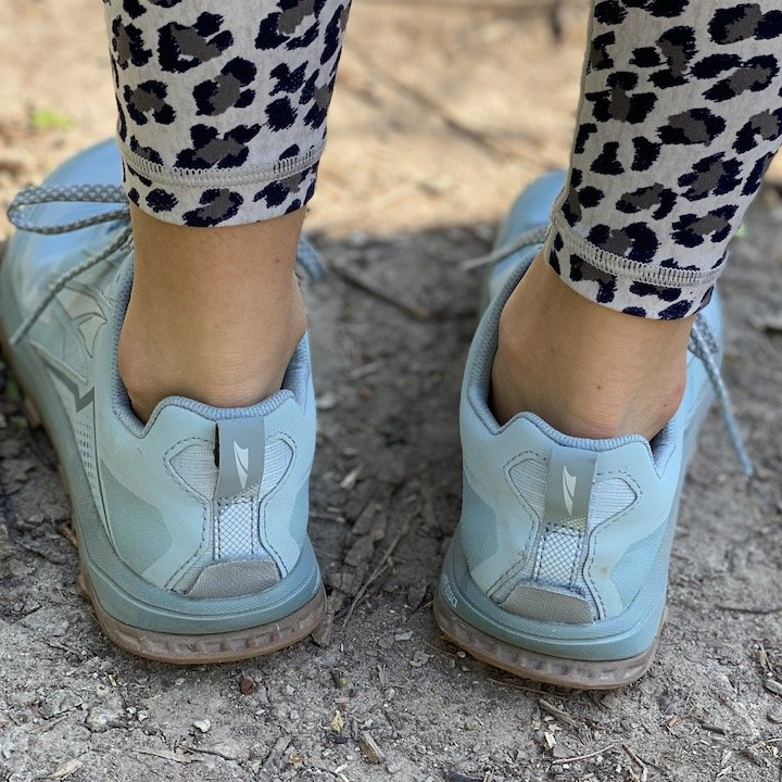 A close up of the back of a woman's legs in leopard leggings wearing Altra Lone Peak blue zero drop foot shaped trail shoes with a wide toe box.